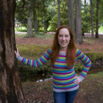 Caitlyn is standing in a local park with one hand on a tree and the other on her hip. She's wearing a striped sweater and jeans smiling directly at the camera.