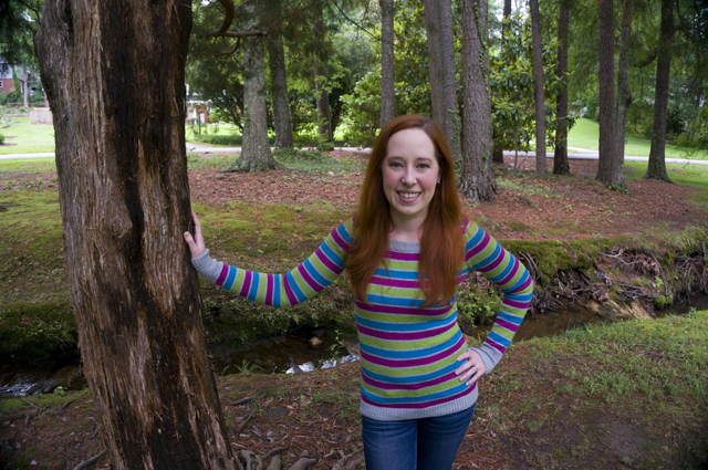 Caitlyn is standing in a local park with one hand on a tree and the other on her hip. She's wearing a striped sweater and jeans and smiling directly at the camera.