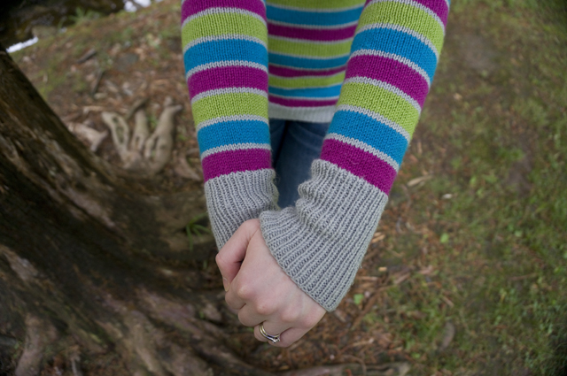 A close-up of Caitlyn's forearms and hands. Her striped sweater has wider fuchsia, turquoise, and lime stripes alternating with thinner light grey stripes, and light grey ribbed cuffs.