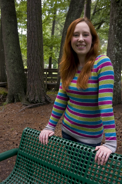 Caitlyn is resting her hands on the back of a green park bench and smiling at the camera. The stripes on her sweater aligned across the body and sleeves, and the ribbing on the cuffs is echoed at the hem.