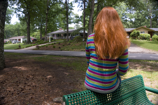 Caitlyn is sitting on a green park bench facing away from the camera toward houses in the distance.