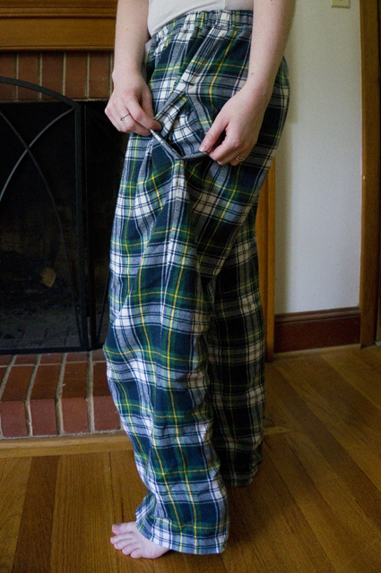 Side view of the tartan pajama pants with the pocket pulled open to reveal tartan pocket bags