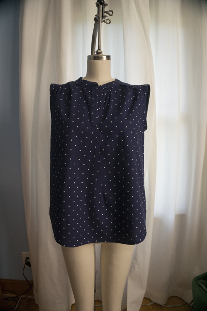 The front of a woman's sleeveless summer top with a half placket and curved hem