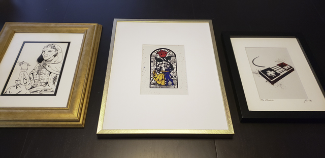 Left, a pen and ink drawing of a hooded, roguish woman with a dagger and sack; center, a selectively colored line art print of Beast and Belle dancing; right, a black and white print of an original Nintendo controller