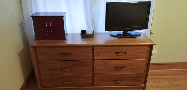 A wooden dresser, surmounted by a TV, jewelry chest, and small bowl of keychains, with an otherwise clean surface