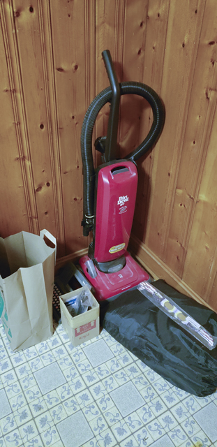 A pile of items, including an upright vacuum cleaner, an inflatable mattress, a paper bag of clothes, and a small cardboard box of electronics, sitting on a linoleum floor against a wood-paneled wall