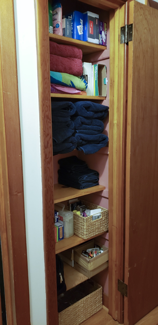 The inside of the same linen closet after being organized, with empty space on two of the six shelves
