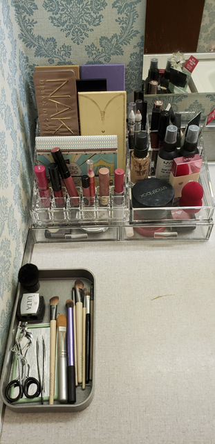 Stackable clear acrylic makeup storage holds a variety of lipsticks, eyeshadow palettes, and creams, and another plastic tray holds makeup brushes and cosmetic tools