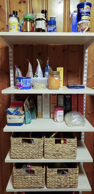 A freestanding pantry shelf unit neatly organized into groups of condiments, breakfast foods, grains and pastas, and sweet and salty snacks