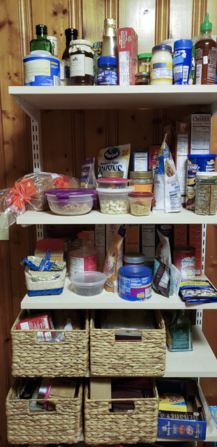 A freestanding pantry shelf unit with a hodgepodge of boxes, jars, and food storage containers