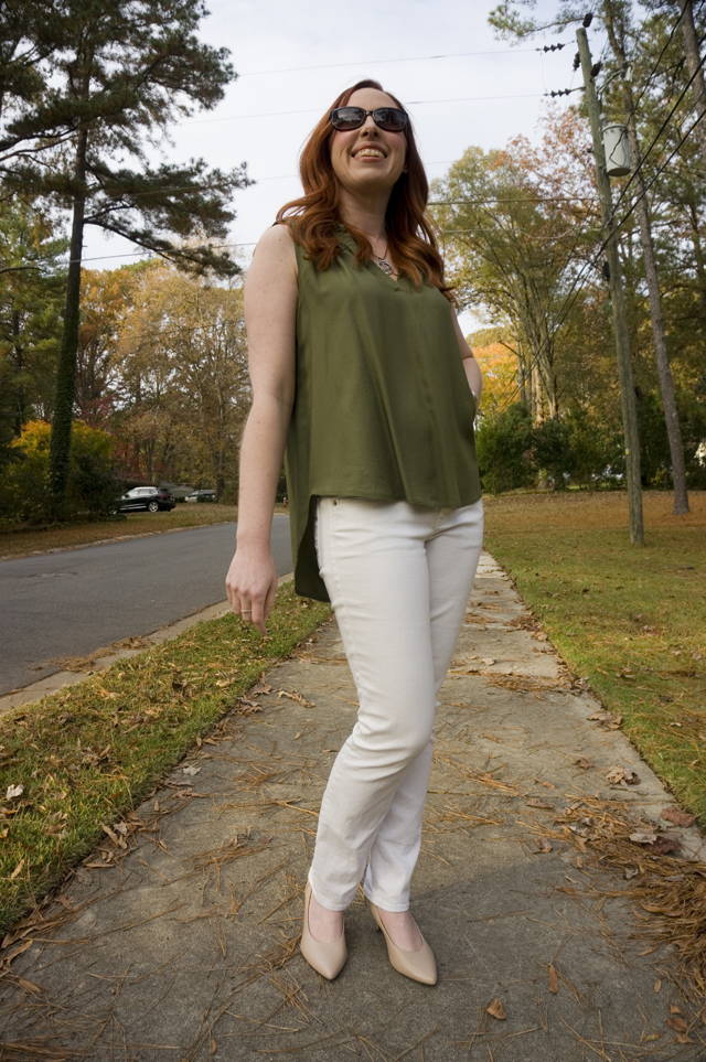 Caitlyn is standing on residential sidewalk wearing a sleeveless summer blouse, white jeans, nude pumps, and sunglasses