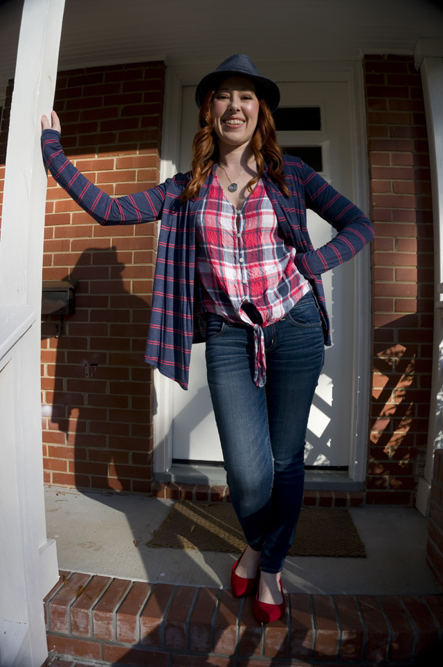 Caitlyn stands on her front porch smiling and wearing a denim hat, open-front cardigan, tie-front button-up shirt, jeans, and pointed-toe flats