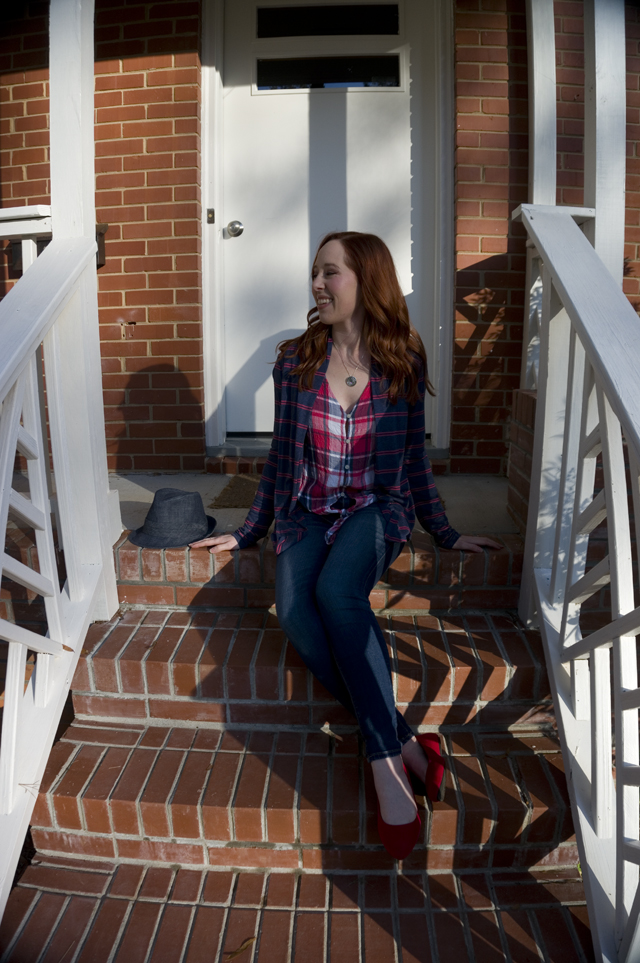 Caitlyn sits on her front porch next to a denim hat, smiling and wearing an open-front cardigan, tie-front button-up shirt, jeans, and pointed-toe flats