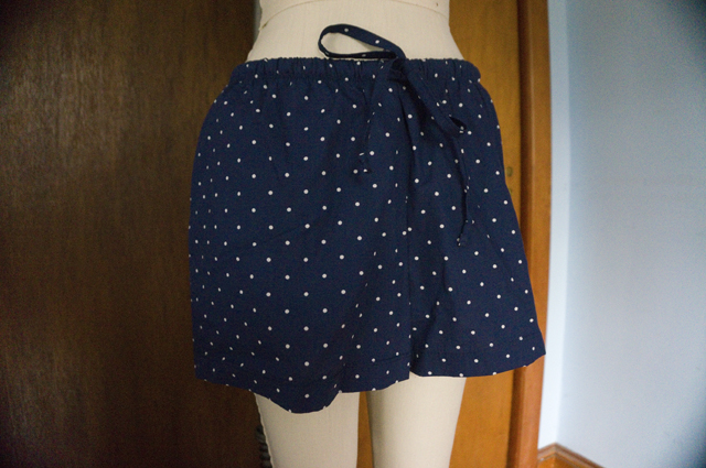 The front of a pair of drawstring pajama shorts hanging on a dress form