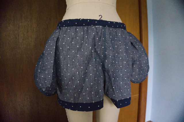 A pair of pajama shorts turned inside-out on a dress form to reveal in-seam pocket bags and the stitching throughout