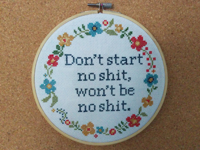 "A cross stitch of the words ""Don't start no shit, won't be no shit"" surrounded by a floral border and framed in a hoop"
