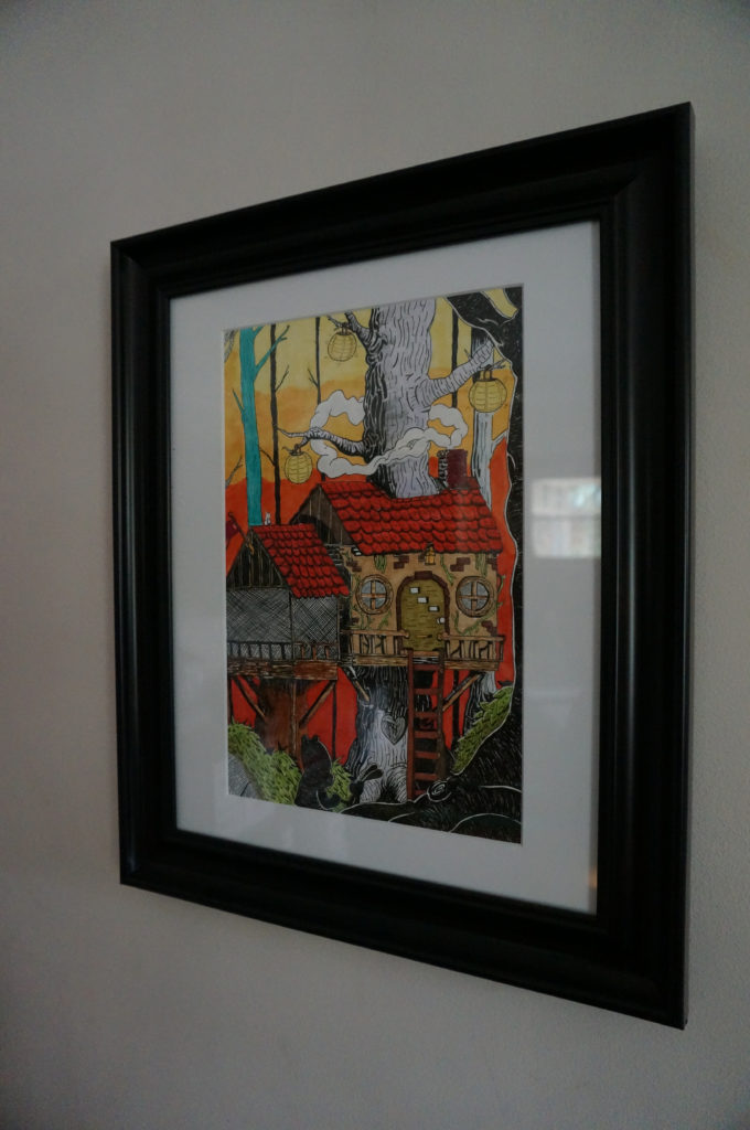 A framed illustration of a cottage-style treehouse with the silhouettes of a cartoon bear and rabbit in the foreground