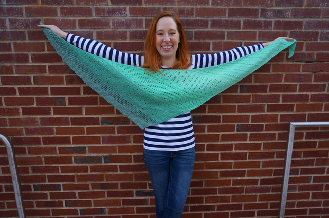 Caitlyn holds up a shawl made with Freia Handpaints yarn to show the full wingspan and different lace patterns