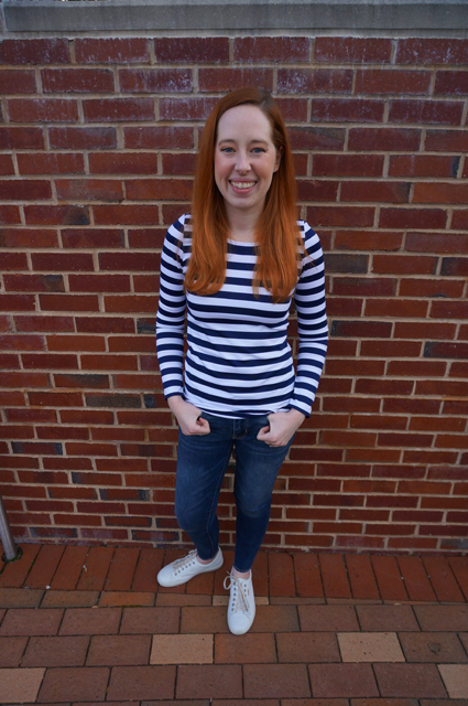 Caitlyn is smiling as she stands with her thumbs hooked through her belt loops and shows off the long-sleeve striped t-shirt she made