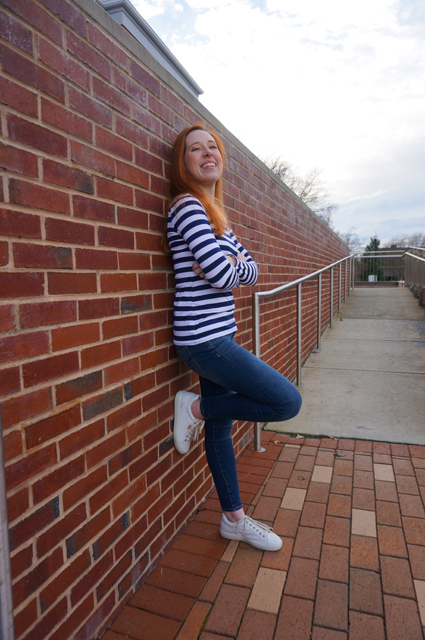 Caitlyn is standing with her back and one foot against a brick wall, arms crossed but smiling as she shows off the long-sleeve striped t-shirt she made
