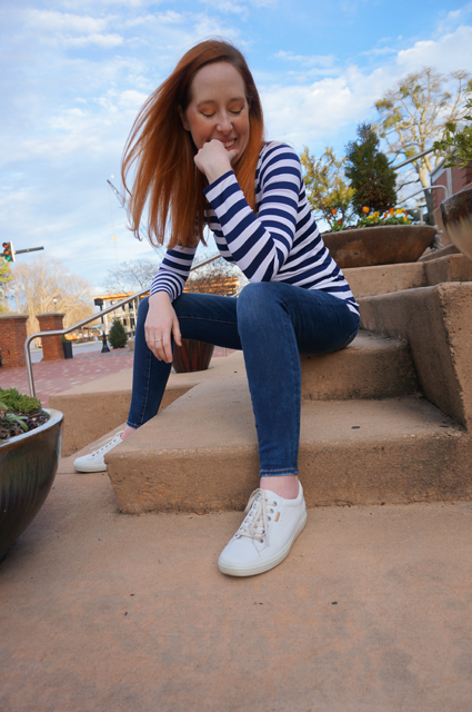 Caitlyn is wearing a long-sleeve striped t-shirt she made, sitting on the steps of a public building, and smiling with her eyes closed as though thinking of a secret