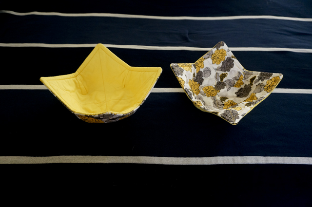 Two bowl cozies with a yellow and grey floral exterior fabric and a solid yellow interior fabric
