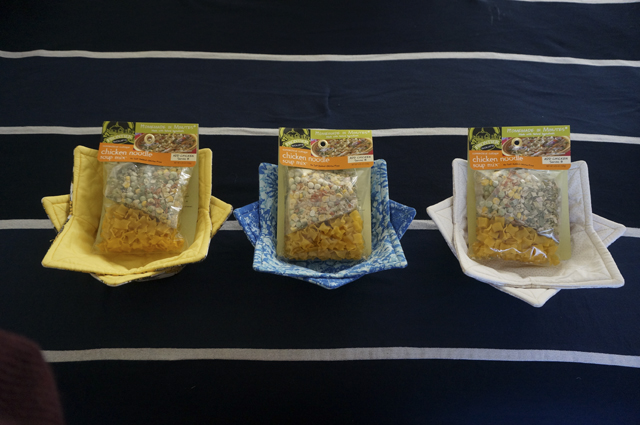 Three pairs of nested bowl cozies, each holding a bag of pre-packaged soup mix