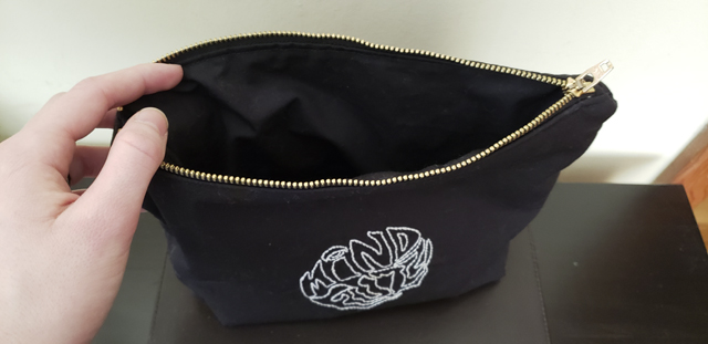 A black zippered pouch with the zipper opened to reveal a cleanly finished interior lined in the same black fabric