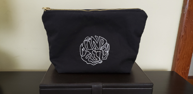 "A black zippered pouch with outline of the words ""Mind Fuzz"" embroidered in white in a circle in the center of the pouch"