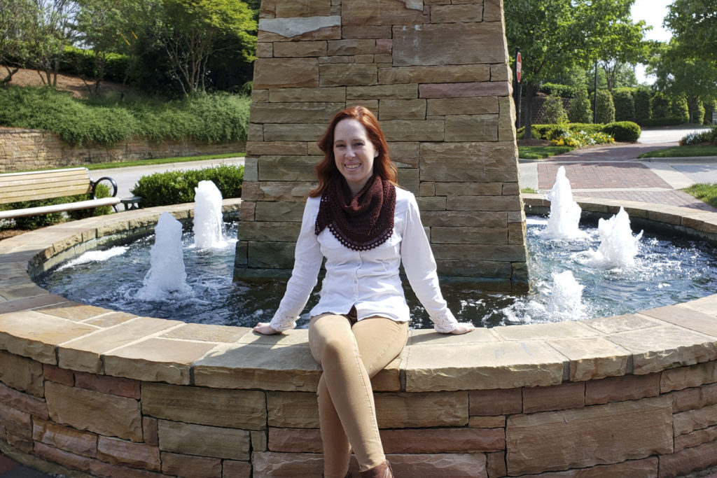 Caitlyn is sitting on a stone ledge around a fountain. She is wearing her Henslowe shawl wrapped around her neck like a bandana.