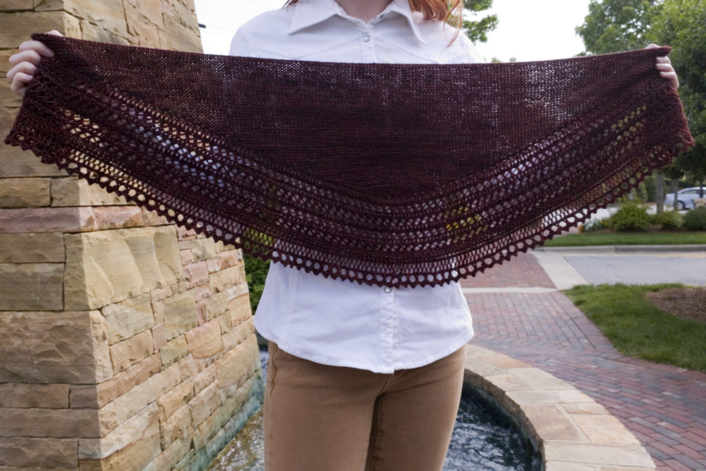 A close-up of Caitlyn holding the Henslowe shawl to show the shape is a shallow, rounded triangle