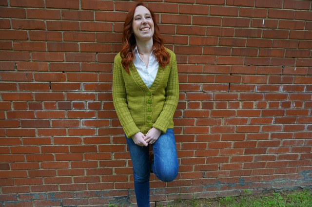 Caitlyn is leaning against a brick wall and wearing her CustomFit Stonington cardigan by Amy Herzog