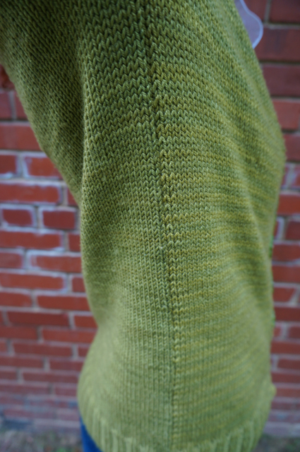A close-up up of the side seam of Caitlyn's CustomFit Stonington, showing how the yarn's dye lots differ on the front and back