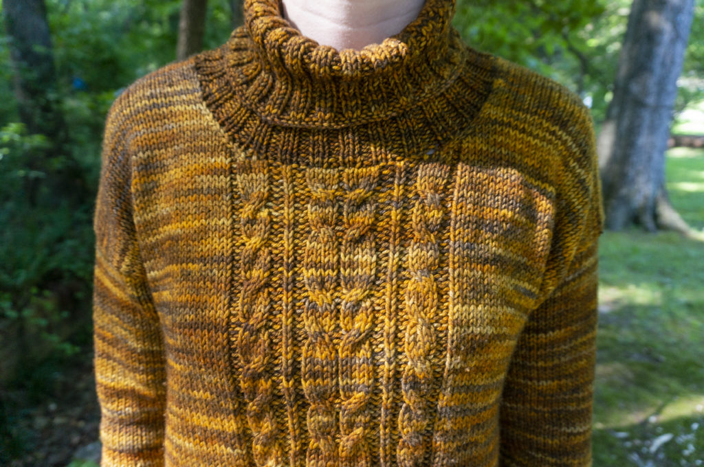 A golden-brown sweater with a central cable panel, turtleneck, and long sleeves
