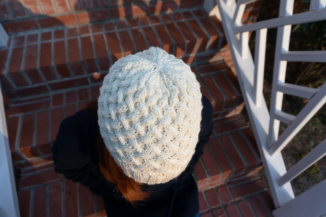 A top-down view of cable knit hat in off-white yarn being worn on the head