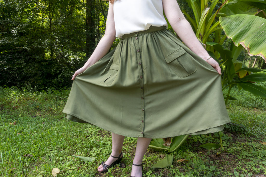 A sage green below-the-knee button-front skirt with a gathered waist and patch pockets