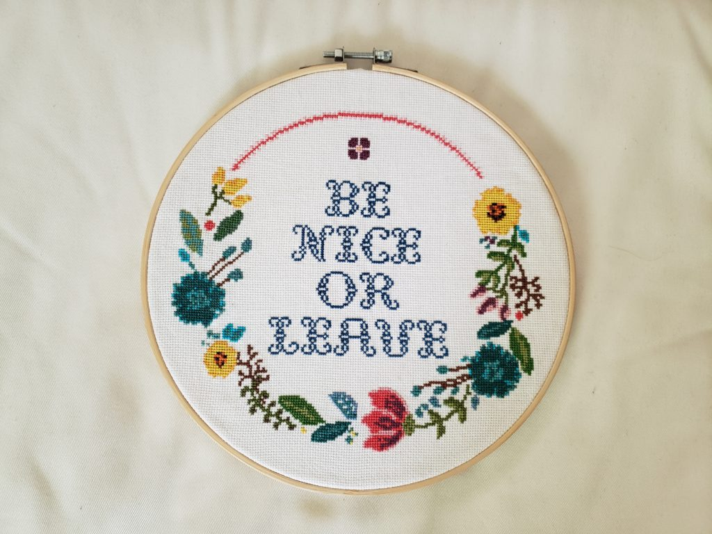 Cross stitch with a floral border framed in a wooden hoop