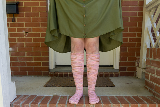Knee socks made with a light pink, lavender, and tan variegated yarn