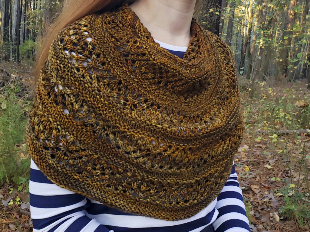 A golden-brown circular shawl with alternating bands of stockinette and a diamond lace motif